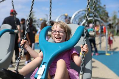 Lydia Stagg, age 6, smiles as she swings at Liberty Playground following the ribbon-cutting.